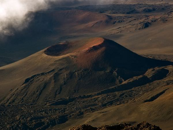Haleakala, a giant shield volcano, forms the eastern bulwark of the island of Maui. In Earth's deep past, periods of increased volcanism would've helped the Earth cool, like a radiation releasing steam. Credit: National Geographic/Cathy Roberts
