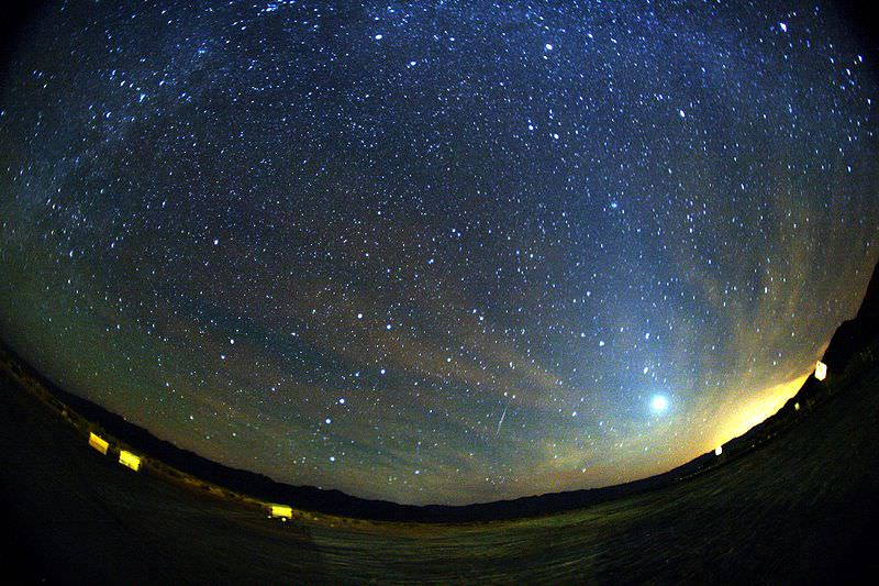 A green and red Orionid meteor striking the sky below Milky Way and to the right of Venus. Zodiacal light is also seen at the image The trail appears slightly curved due to edge distortion in the lens. Taken by Mila Zinkova