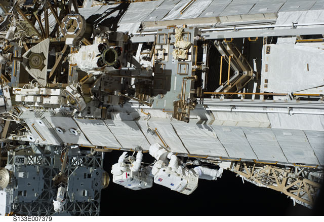 Astronauts Steve Bowen and Alvin drew work in tandem on one of the truss sections of the ISS during the first spacewalk of the STS-133 mission. Credit: NAS