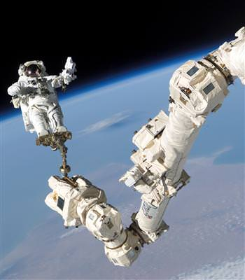 Canadarm2, the huge robotic arm on the International Space Station holds astronaut Stephen Robinson during the STS-114 mission. Credit: NASA
