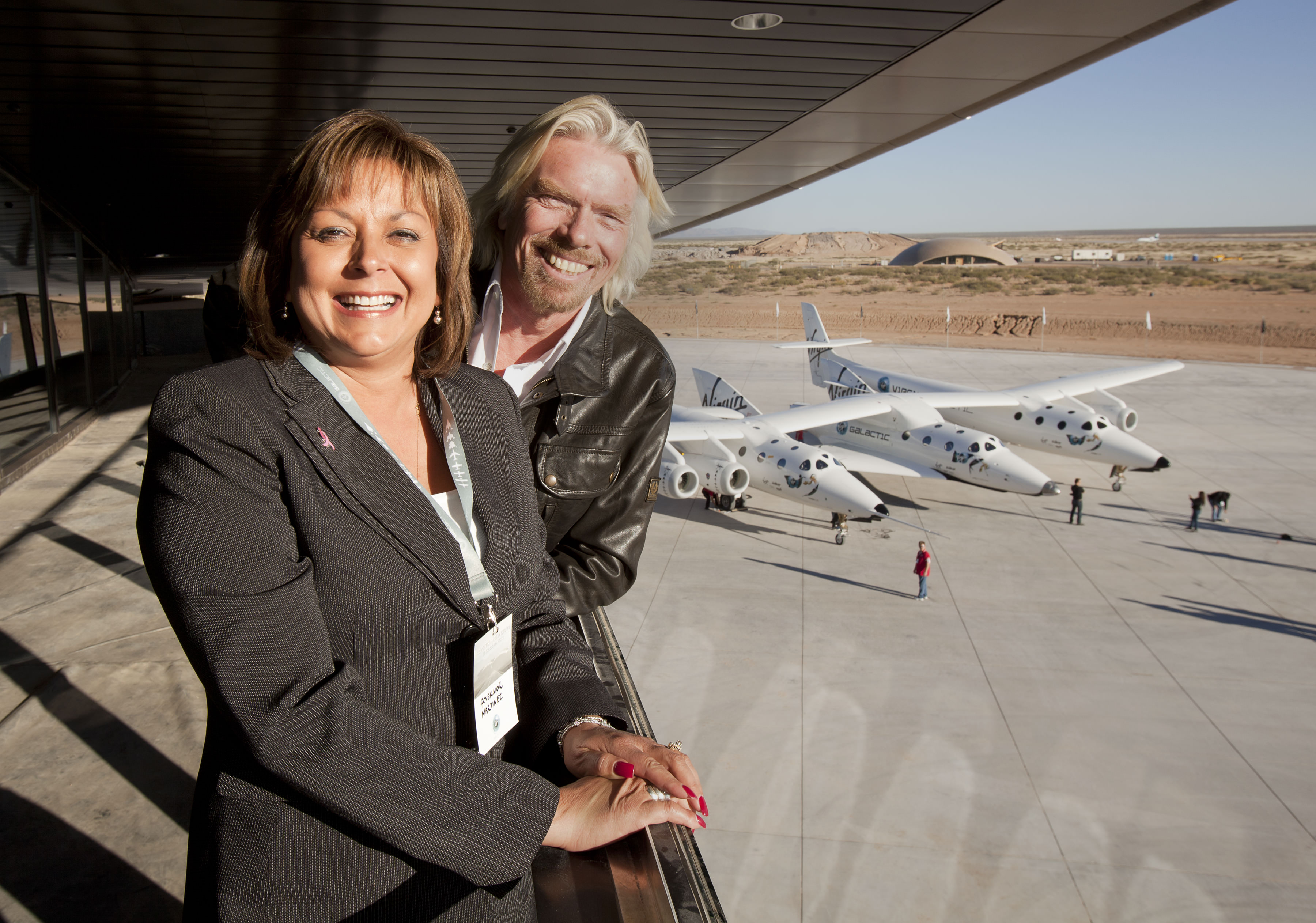 New Mexico Governor Susana Martinez and Sir Richard Branson pose for photographer on the balcony of the new Spaceport Hangar, Monday October 17, 2011 near Las Cruces, New Mexico. It was part of a dedication and christening of the hangar to Virgin Galactic. Credit: Mark Greenberg