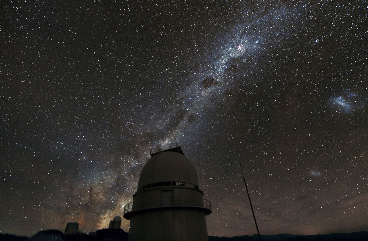 The night sky above the Danish 1.54-metre telescope at ESO's La Silla Observatory. The Magellanic Clouds are visible to the right of the central bar of the Milky Way. Credit:  ESO/Z. Bardon