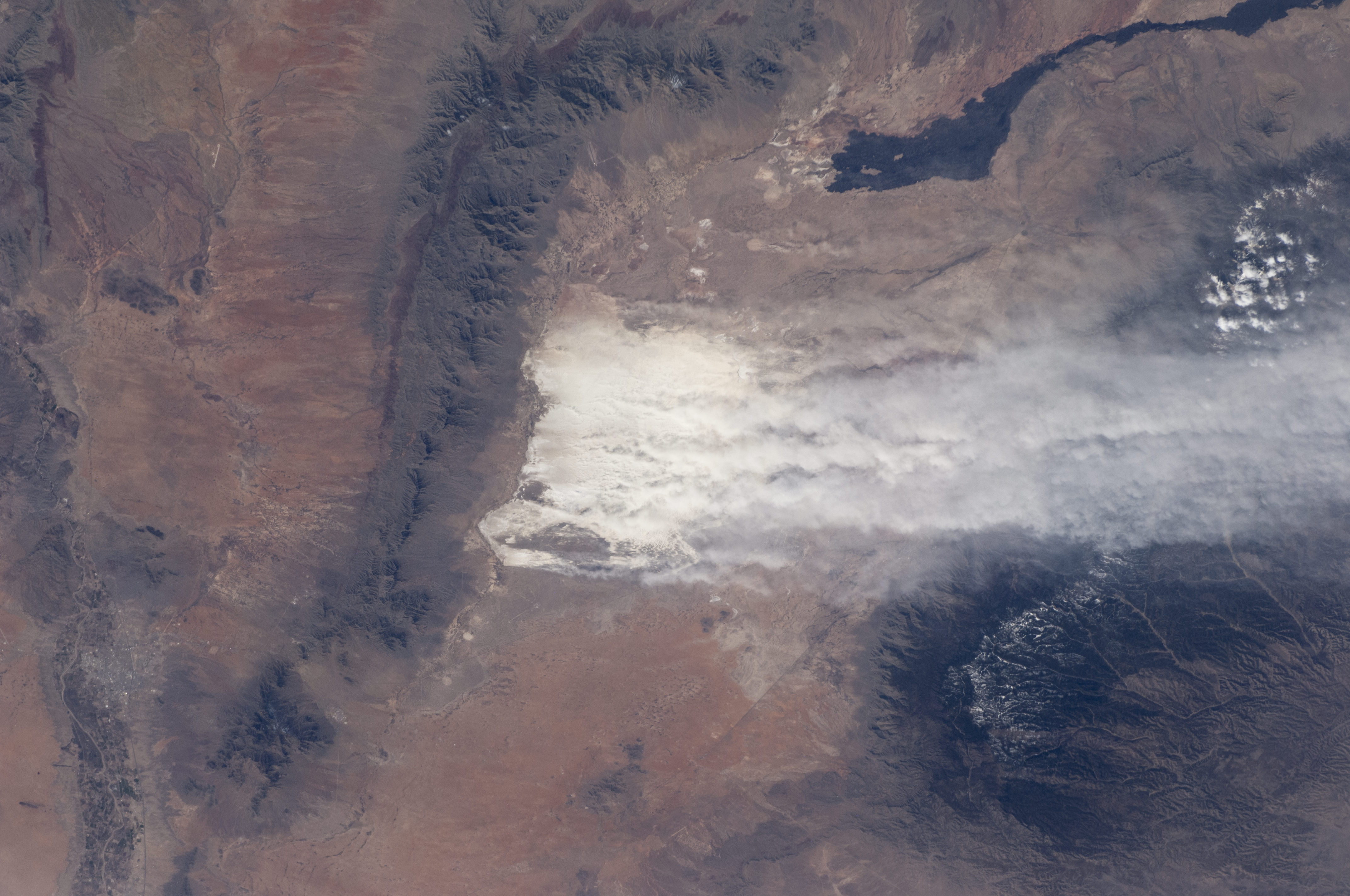 Driven by southwesterly winter winds, dust from the White Sands dune field in New Mexico rises thousands of feet from the valley floor and drifts over the snowy peaks of the Sacramento Mountains. Credit: NASA