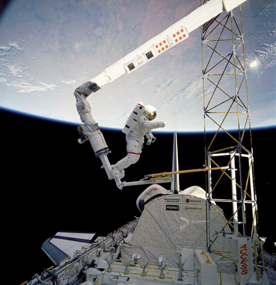 Jerry Ross on the end of the space shuttle's RMS during STS-61B in 1985, demonstrating the feasibility of assembling structures in space. Credit: NASA.