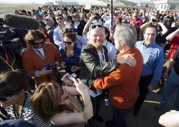 "Sir Richard Branson hugs designer Burt Rutan as they are surrounded by employees of Virgin Galactic, The SpaceShip Company and Scaled Composites watch as Virgin Galactic's SpaceShip2 streaks across the sky under rocket power, its first ever since the program began in 2005. Burt's wife Tonya Rutan is at right taking their photo. The spacecraft was dropped from its ""mothership"", WhiteKnight2 over the Mojave, CA area, April 29, 2013 at high altitude before firing its hybrid power motor. Virgin Galactic hopes to become the first commercial space venture to bring multiple passengers into space on a regular basis."