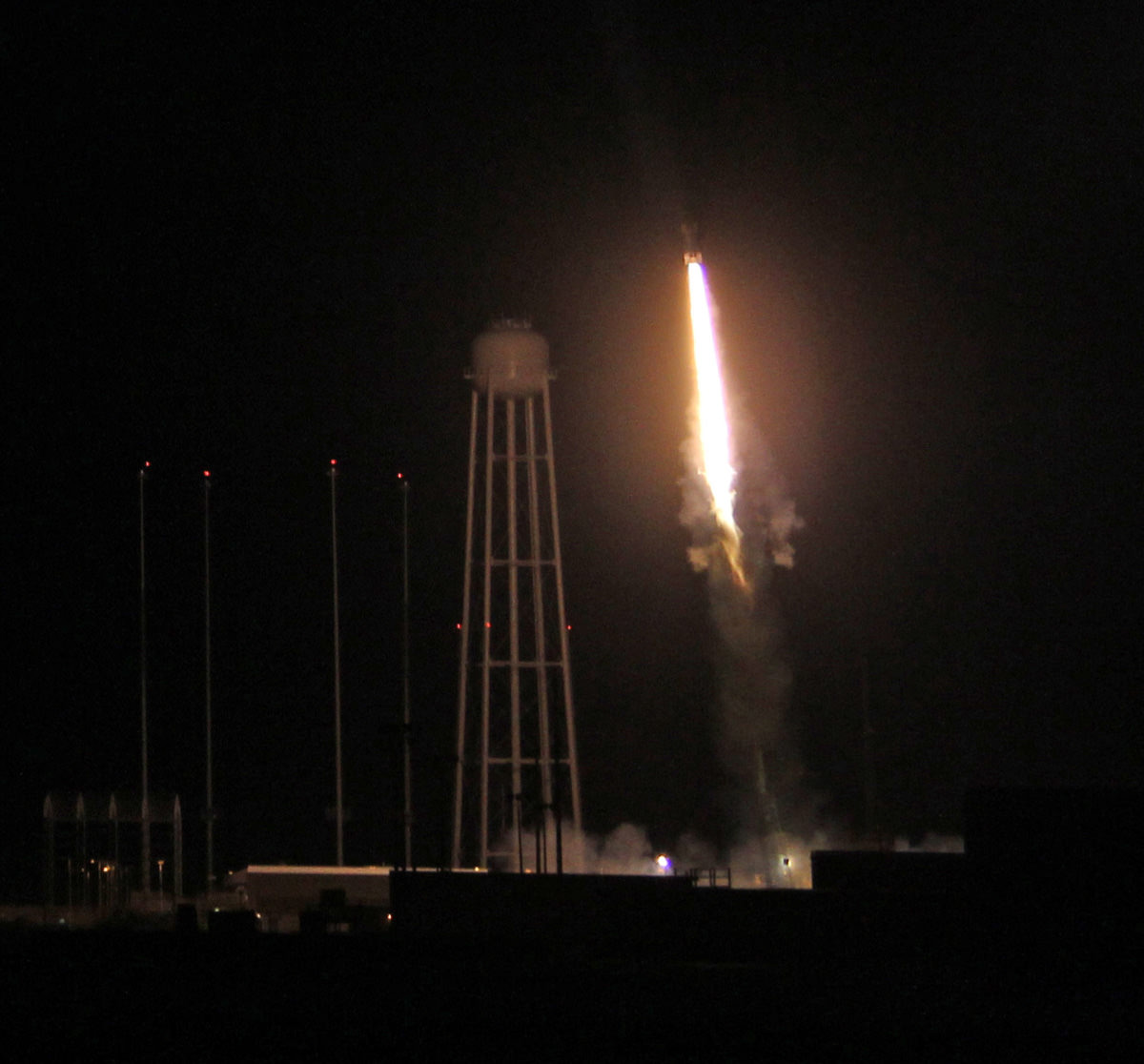 Night time blast off of 4 stage NASA Black Brant XII suborbital rocket at 11:05 p.m. EDT on June 5, 2013 from the NASA Wallops Flight Facility carrying the CIBER astronomy payload to study when the first stars and galaxies formed in the universe.  The Black Brant soars above huge  water tower at adjacent Antares rocket launch pad at NASA Wallops.  Credit: Ken Kremer- kenkremer.com