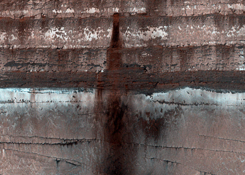 Loose soil, dust and rock stains an icy cliffside on Mars (NASA/JPL/University of Arizona)