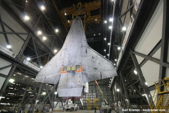 Full belly view of Space Shuttle Discovery coated with thousands of protective heat shield tiles in the transfer aisle of the VAB where it was processed for final launch on STS-133 mission.  Note two rectangular attach points holding left and right side main separation bolts. Credit: Ken Kremer - kenkremer.com