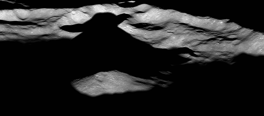 An oblique view from the Lunar Reconnaissance Orbiter of Icarus Crater on the Moon. The shadow created by the unusual central peak in the crater is reminiscent of a certain Star Wars character.  Icarus is approximately 94 km in diameter. Credit: NASA/GSFC/Arizona State University.