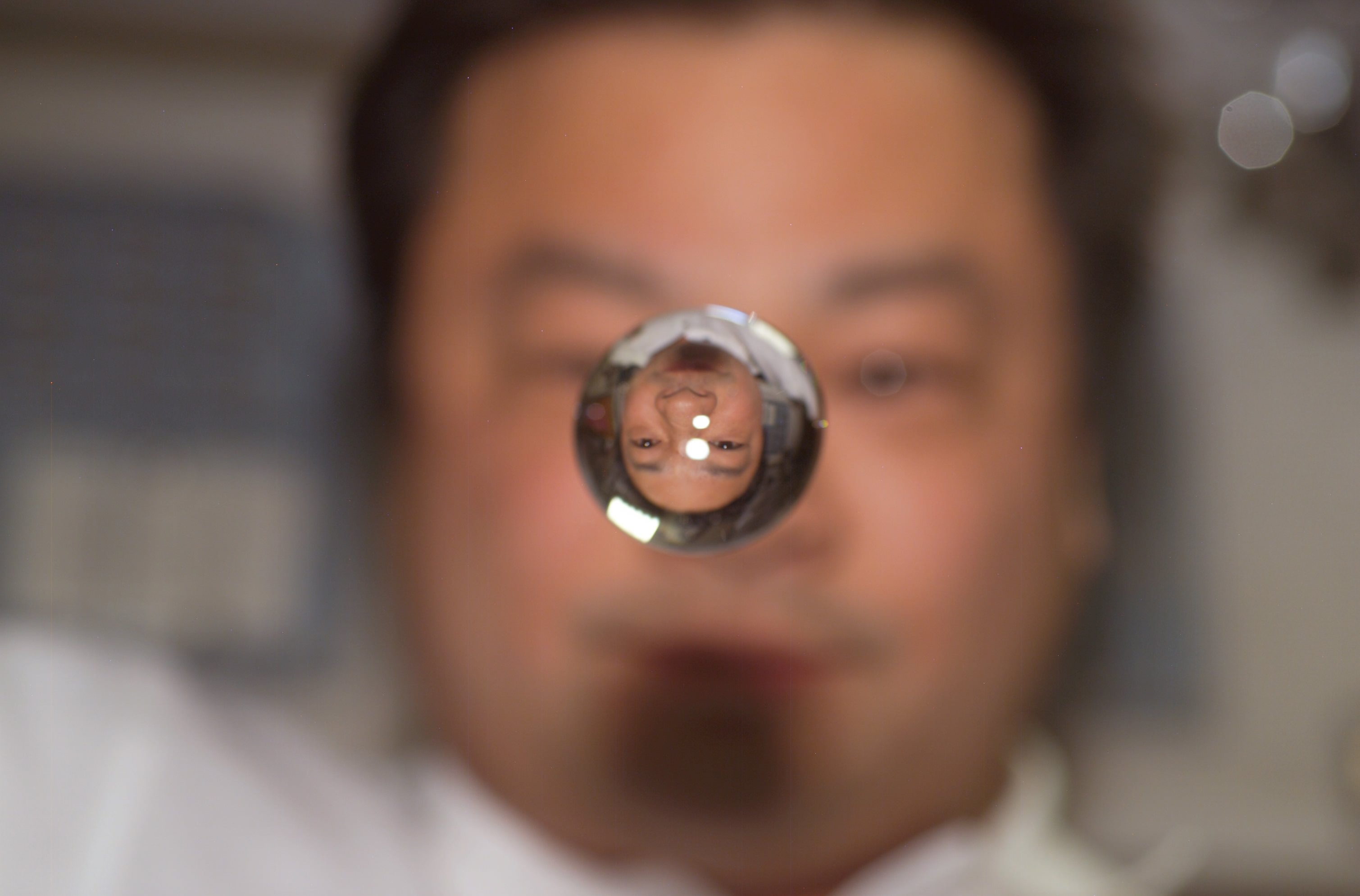 Expedition 10 commander Leroy Chiao is reflected in a water sphere on board the International Space Station in 2004. Credit: NASA
