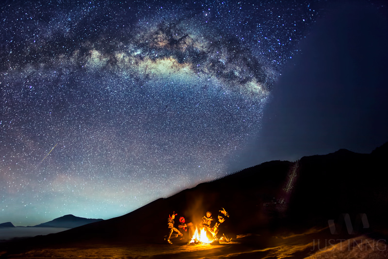 Porters at Mt. Bromo in Indonesia warm themselves by a fire as an Eta Aquarid meteor streaks overhead on May 6, 2014. Credit and copyright: Justin Ng.