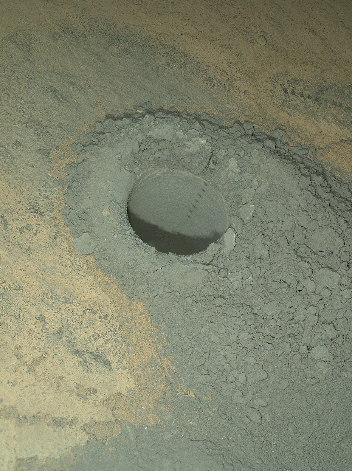 The Mars Hand Lens Imager on NASA's Curiosity Mars rover provided this nighttime view of a hole produced by the rover's drill and, inside the hole, a line of scars produced by the rover's rock-zapping laser. The hole is 0.63 inch (1.6 centimeters) in diameter.  The camera used its own white-light LEDs to illuminate the scene on May 13, 2014.  Credit:  NASA/JPL-Caltech/MSSS