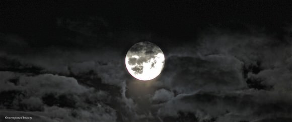 An over-exposed beauty showing the full Moon rising through the clouds on July 12, 2014 near  Bromsgrove, England, United Kingdom. Credit and copyright: Sarah and Simon Fisher.