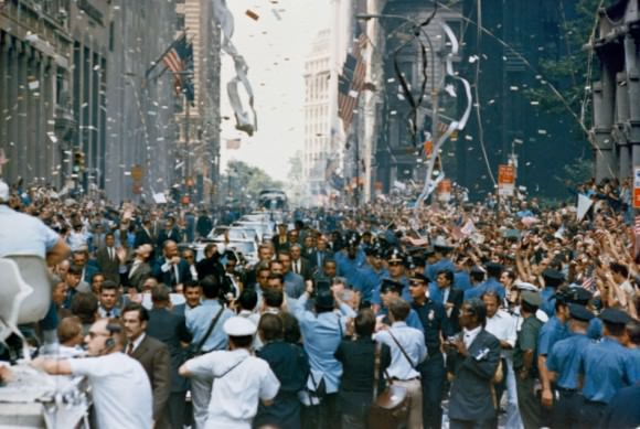 Apollo 11 Welcome. New York City welcomes the Apollo 11 crew in a ticker tape parade down Broadway and Park Avenue. Pictured in the lead car, from the right, are astronauts Neil A. Armstrong, Buzz Aldrin and Michael Collins. The three astronauts teamed for the first manned lunar landing, on July 20, 1969.  Credit: NASA