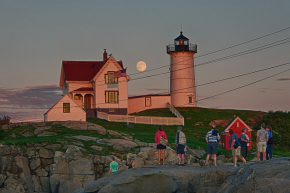 People watch the nearly 'super' Moon rise on August 9, 2014 near a lighthouse.  Credit and copyright:  Will Nourse.