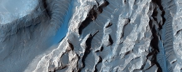 "A close-up of ""chaotic terrain"" in Valles Marineris imaged by the Mars Reconnaissance Orbiter's HiRISE camera. Wind or fluid may have further shaped this region, which could be related to possible signs of an ancient lake found in other regions of Valles Marineris. Credit: NASA/JPL/University of Arizona"