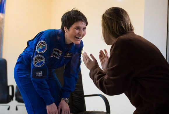 Prior to the launch of Expedition 42 in November 2014, Samantha Cristoforetti (left, European Space Agency) speaks with a loved one through the glass at a pre-launch press conference. Credit: NASA/Aubrey Gemignani