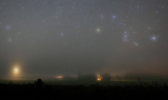 Color by fog. The colors of stars are accentuated when photographed through fog or light cloud. Orion at right with the crescent moon at lower left. Credit: Bob King
