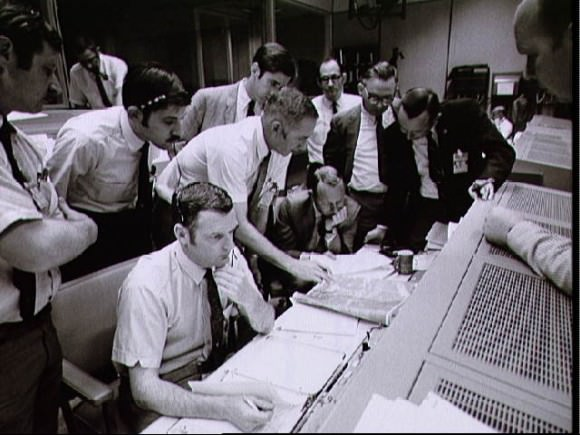 A group of flight controllers gather around the console of Shift 4 Flight Director Glynn Lunney (seated, nearest camera) in the Mission Operations Control Room. Their attention is drawn to a weather map of the proposed landing site in the South Pacific. Among those looking on is Christopher Kraft, Manned Spacecraft Center Deputy Director, (standing, in black suit, right). Credit: NASA.