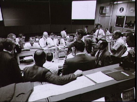Overall view showing some of the activity in the Mission Operations Control Room during the final 24 hours of the Apollo 13 mission. From left to right are Shift 4 Flight Director Glynn Lunney, Shift 2 Flight Director Gerald Griffin, Astronaut and Apollo Spacecraft Program Manager James McDivitt, Director of Flight Crew Operations Deke Slayton and Shift 1 Flight Surgeon Dr. Willard Hawkins. Credit: NASA.