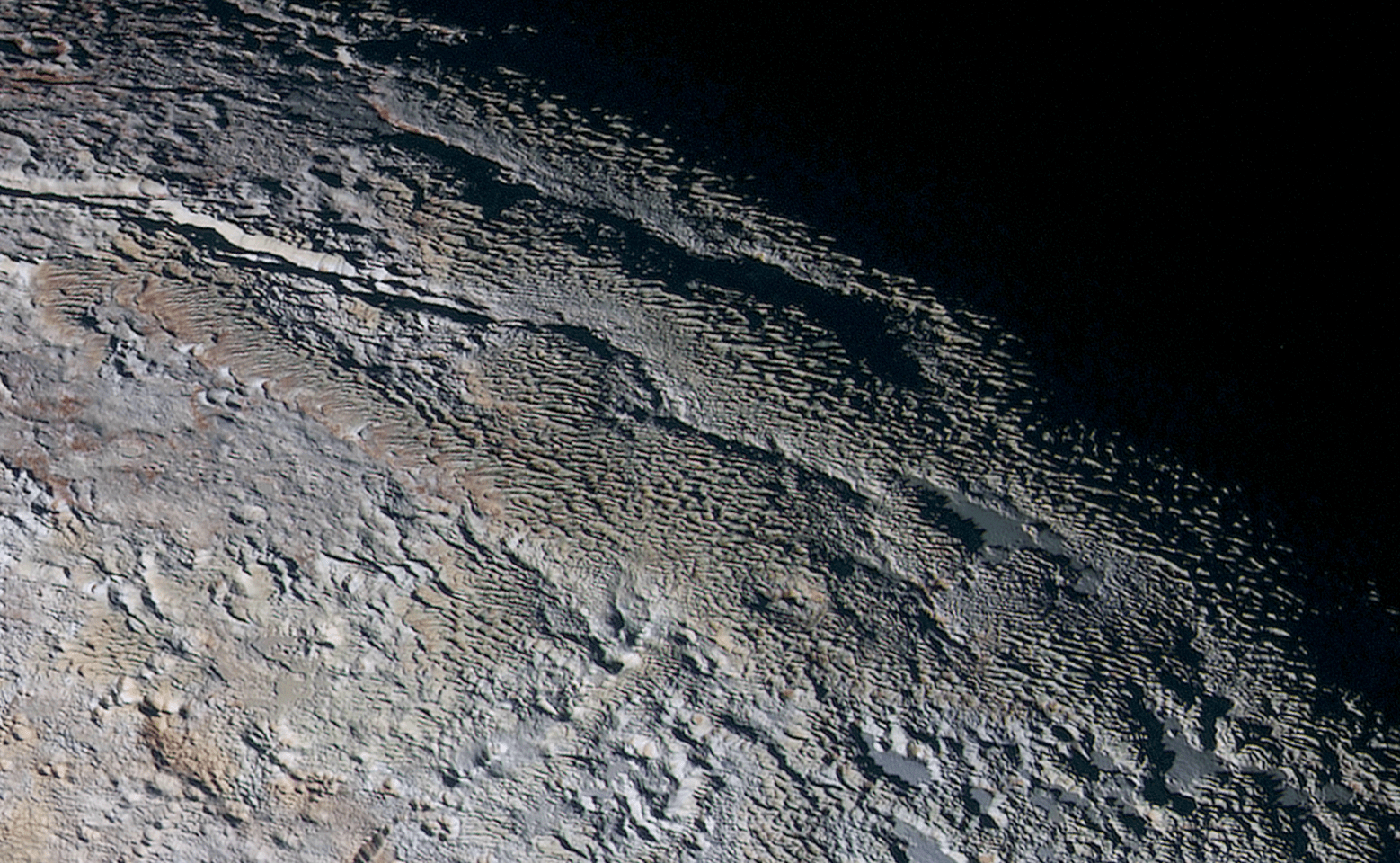 This color image of Pluto taken by NASA's New Horizons spacecraft shows rounded and bizarrely textured mountains, informally named the Tartarus Dorsa, rise up along Pluto's terminator and show intricate but puzzling patterns of blue-gray ridges and reddish material in between. This view, roughly 330 miles (530 kilometers) across, combines blue, red and infrared images taken by the Ralph/Multispectral Visual Imaging Camera (MVIC) on July 14, 2015, and resolves details and colors on scales as small as 0.8 miles (1.3 kilometers).   Credits: NASA/JHUAPL/SWRI