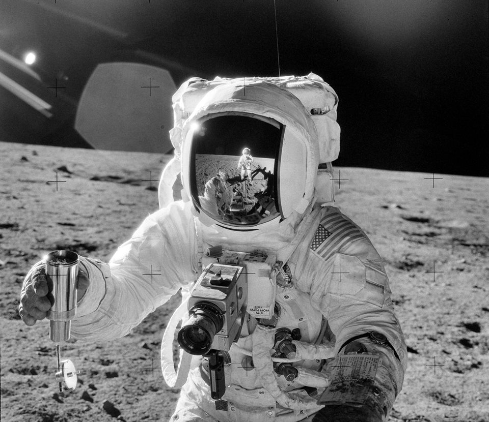 Astronaut Alan L. Bean holds a Special Environmental Sample Container filled with lunar soil collected during the second Apollo 12 extravehicular activity (EVA) conducted by astronauts Charles Conrad Jr., commander, and Bean, lunar module pilot. Conrad, who took this picture, is reflected in Bean's helmet visor. November 20, 1969. Credit: NASA/JSC.