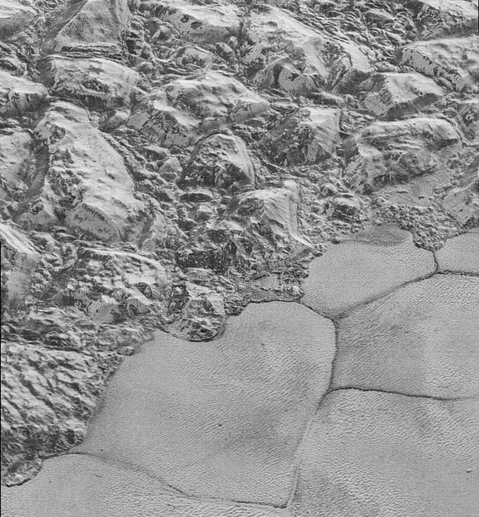 The Mountainous Shoreline of Sputnik Planum on Pluto. Great blocks of Pluto's water-ice crust appear jammed together in the informally named al-Idrisi mountains. Some mountain sides appear coated in dark material, while other sides are bright. Credit: NASA/Johns Hopkins University Applied Physics Laboratory/Southwest Research Institute.