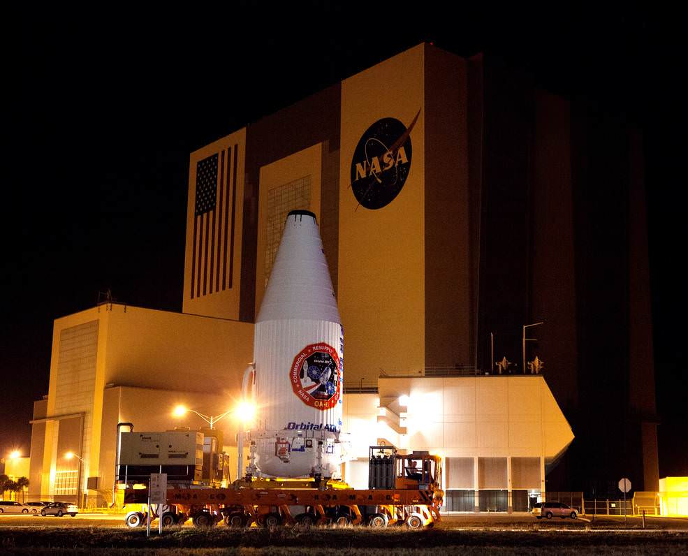 The Cygnus spacecraft for the upcoming Orbital ATK Commercial Resupply Services-6 mission is encapsulated inside its payload fairing as it moves past the Vehicle Assembly Building at NASA's Kennedy Space Center in Florida. It is being moved to Space Launch Complex-41 at Cape Canaveral Air Force Station.  Credits: NASA/Dimitrios Gerondidakis