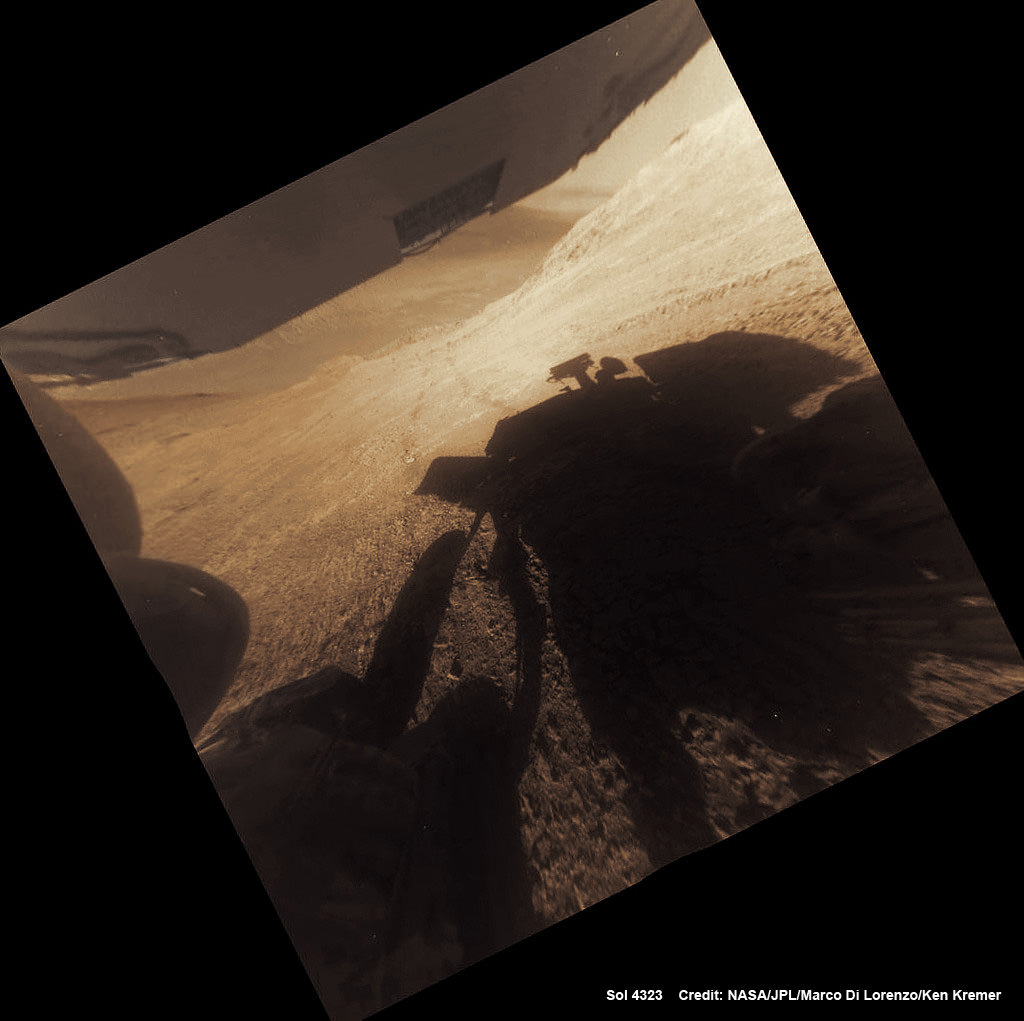 "A shadow and tracks of NASA's Mars rover Opportunity appear in this March 22, 2016, colorized hazcam camera image, which has been rotated 13.5 degrees to adjust for the tilt of the rover. The hillside descends to the left into ""Marathon Valley."" The floor of Endeavour Crater is seen beneath the underside of a solar panel.  Credits: NASA/JPL-Caltech/Marco Di Lorenzo/Ken Kremer/kenkremer.com"