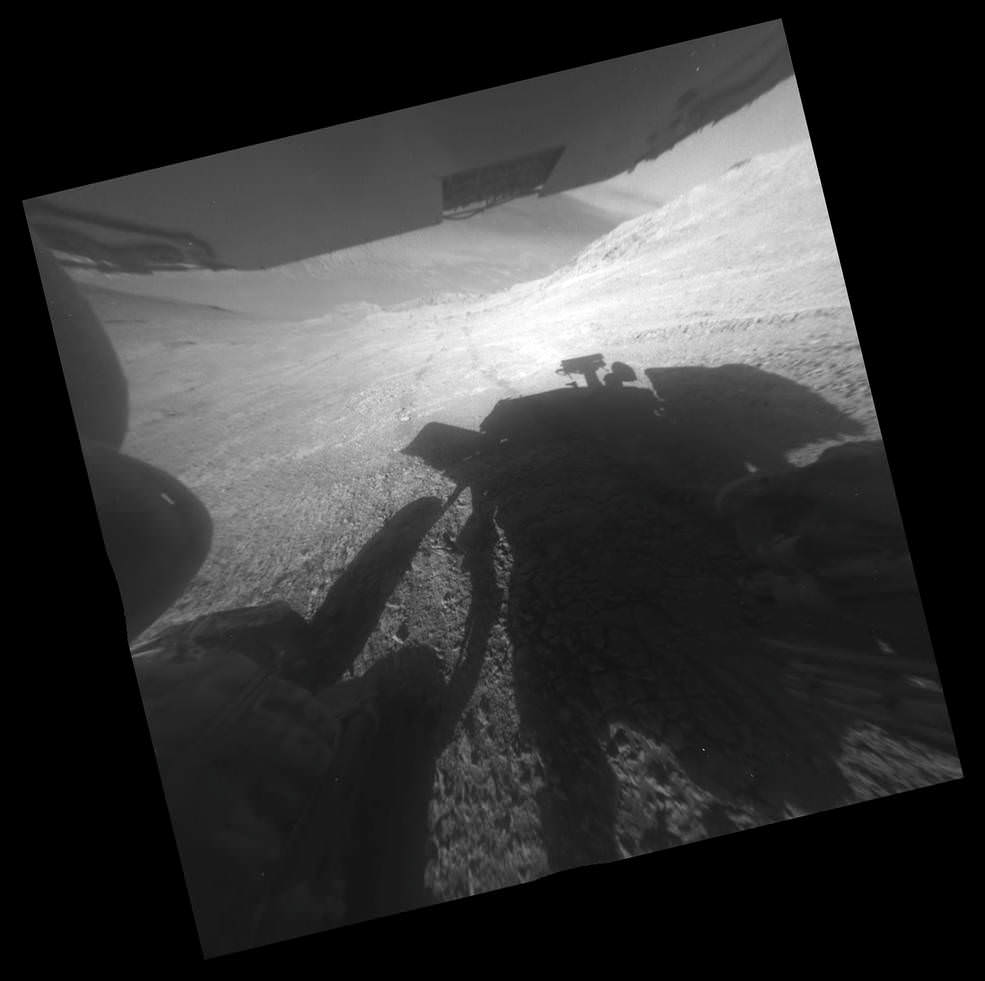 "A shadow and tracks of NASA's Mars rover Opportunity appear in this March 22, 2016, image, which has been rotated 13.5 degrees to adjust for the tilt of the rover. The hillside descends to the left into ""Marathon Valley."" The floor of Endeavour Crater is seen beneath the underside of a solar panel.  Credits: NASA/JPL-Caltech"