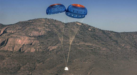 New Shepard's crew capsule is seen descending with its parachutes deployed. The capsule's landing is cushioned by firing rockets after the parachutes have done their job. Image: Blue Origin