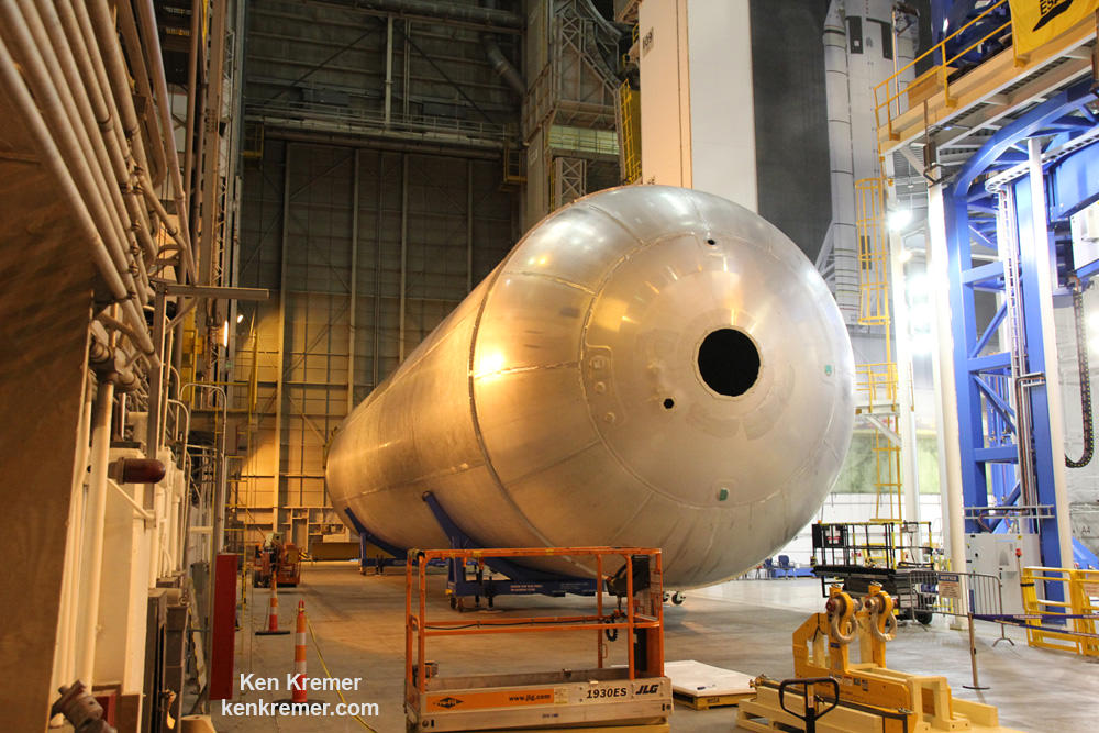 The first liquid hydrogen tank, also called the qualification test article, on NASA's new Space Launch System (SLS) heavy lift rocket lies horizontally beside the Vertical Assembly Center robotic weld machine on July 22, 2016 after final welding was just completed at NASA's Michoud Assembly Facility in New Orleans.  Credit: Ken Kremer/kenkremer.com