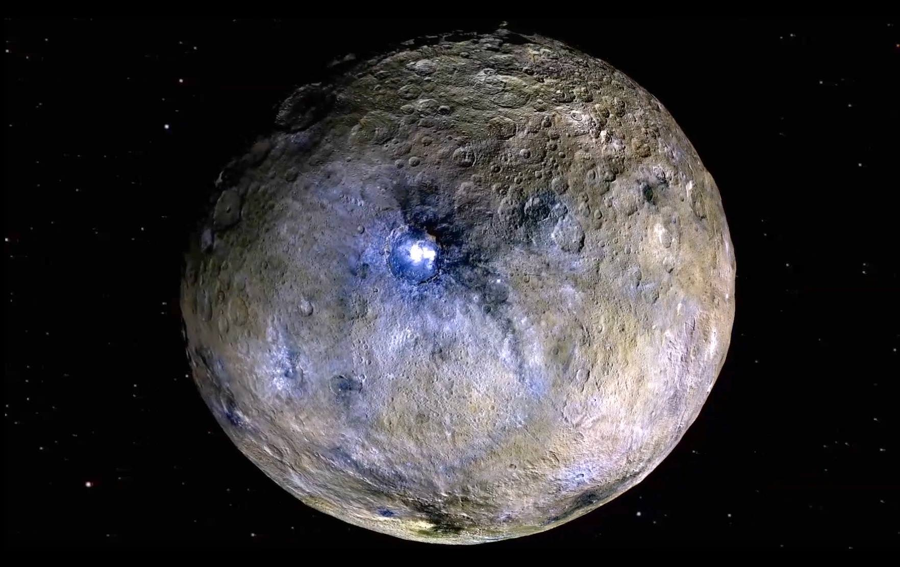 Dwarf planet Ceres is shown in this false-color renderings, which highlight differences in surface materials.  The image is centered on Ceres brightest spots at Occator crater. Image credit: NASA/JPL-Caltech/UCLA/MPS/DLR/IDA