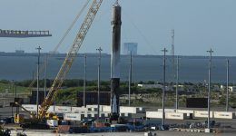 This recovered 156-foot-tall (47-meter) SpaceX Falcon 9 first stage has arrived back into Port Canaveral, FL after successfully launching JCSAT-16 Japanese communications satellite to orbit on Aug. 14, 2016 from Space Launch Complex 40 at Cape Canaveral Air Force Station, Fl. NASA's VAB in the background - as seen from Exploration Tower on Aug. 19.  Credit: Ken Kremer/kenkremer.com