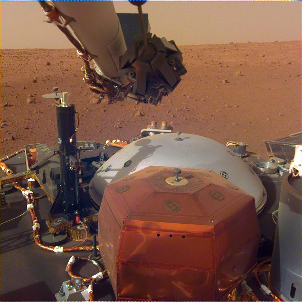 This image was taken by the InSight Lander's Instrument Deployment Camera mounted on the lander's robotic arm. The stowed grapple on the end of the arm is folded in, but it will unfold and be used to deploy the lander's science instrument. The black cylinder on the left is the heat probe, which will drill up to 5 meters into the Martian surface. Image: NASA/JPL-Caltech