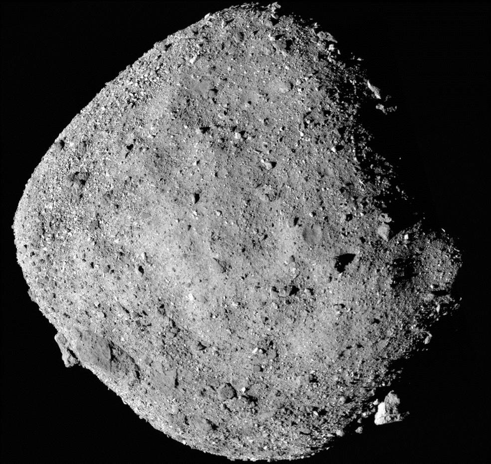 The asteroid Bennu from a distance of 24 km (15) miles captured by the PolyCam on OSIRIS-REx. The spacecraft has detected water on Bennu. On the bottom right in the termination line is the large boulder. The image is a mosaic constructed of 12 images. Image Credit: NASA/Goddard/University of Arizona.