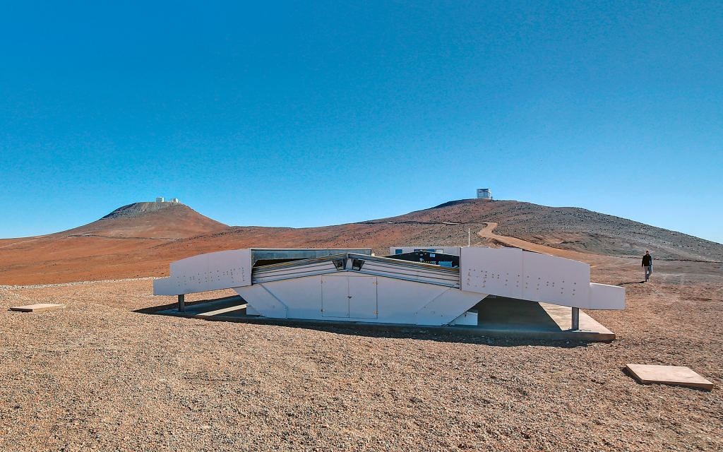 The Next-Generation Transit Survey (NGTS) is located at ESO's Paranal Observatory in northern Chile. This project will search for transiting exoplanets — planets that pass in front of their parent star and hence produce a slight dimming of the star's light that can be detected by sensitive instruments. The telescopes will focus on discovering Neptune-sized and smaller planets, with diameters between two and eight times that of Earth. This image shows the NGTS enclosure in the day. The VISTA (right) and VLT (left) domes can also be seen on the horizon. Image Credit: By ESO/R. Wesson - image pagerelated release (eso1502), CC BY 4.0, https://commons.wikimedia.org/w/index.php?curid=42904088