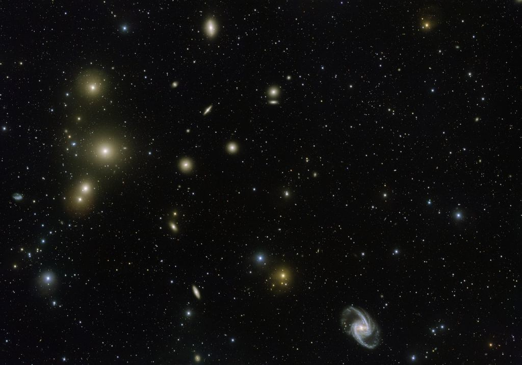 The Fornax Galaxy Cluster is one of the closest of such groupings beyond our Local Group of galaxies. This new VLT Survey Telescope image shows the central part of the cluster in great detail. At the lower-right is the elegant barred-spiral galaxy NGC 1365 and to the left the big elliptical NGC 1399. Image Credit: By ESO. Acknowledgement: Aniello Grado and Luca Limatola - http://www.eso.org/public/images/eso1612a/, CC BY 4.0, https://commons.wikimedia.org/w/index.php?curid=48164737