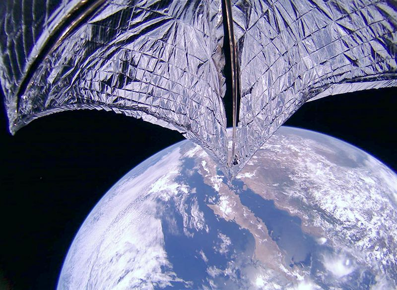 A dramatic image of the sails being deployed, with you-know-what in the background. Image Credit: The Planetary Society.