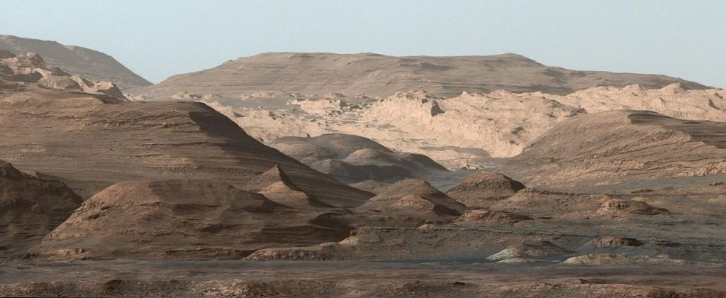 Curiosity's view of Mt. Sharp from 2015. Image Credit: By NASA/JPL-Caltech/MSSS - http://photojournal.jpl.nasa.gov/jpeg/PIA19912.jpg, Public Domain, https://commons.wikimedia.org/w/index.php?curid=43932649