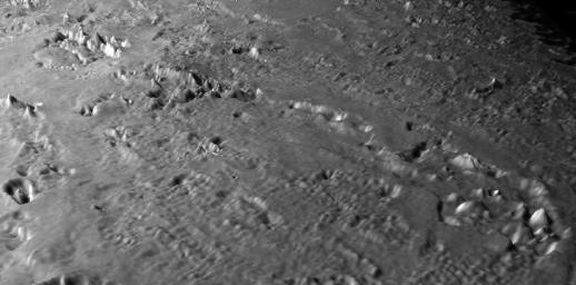 This Voyager 2 images shows a close-up of a prominent chain of volcanic features surrounded by smooth volcanic plains formed by lavas or ash deposits of water or other ices, such as methane or ammonia. The smaller pits and domes are typically 10 kilometers (6 miles) across and have relief of no more than a few hundred meters (several hundred feet). The large depressions at the far left and right of the chain are 50 to 80 kilometers (31 to 50 miles) across. Image Credit: NASA/JPL/Universities Space Research Association/Lunar & Planetary Institute